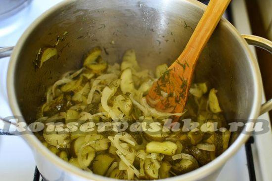 Выкладываем огурцы с луком в глубокую кастрюлю, заливаем маринадом