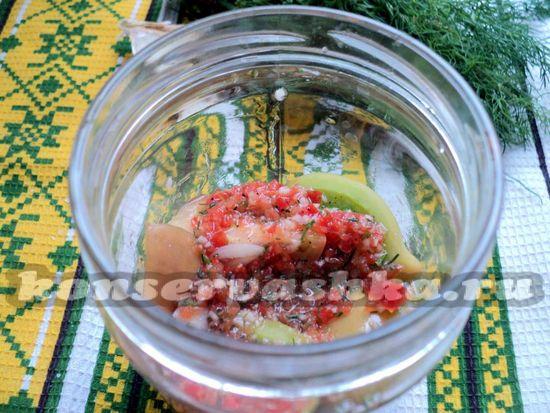 Поочередно заполняем банку бурыми помидорами и чесночно-перечной заправкой