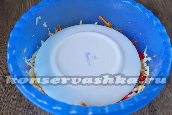 На капусту кладем плоскую тарелку, а сверху ставим банку с водой